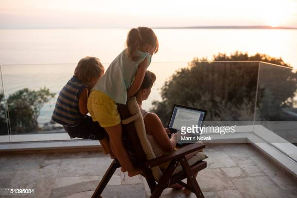 mom managing her office work and kids simultaneously - nomadic people stock pictures, royalty-free photos & images