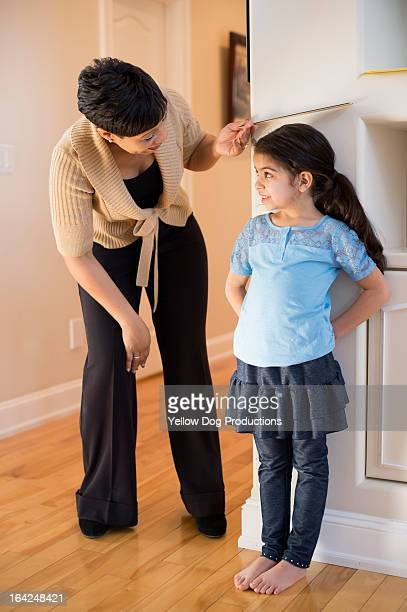 Mom measuring daughter's height against wall