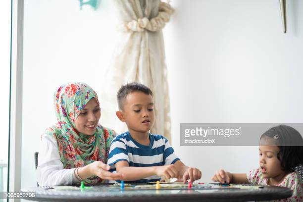 mom playing a board game with her kids - board game stock pictures, royalty-free photos & images