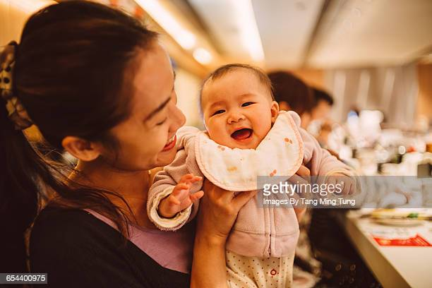 Mom playing joyfully with her baby in restaurant