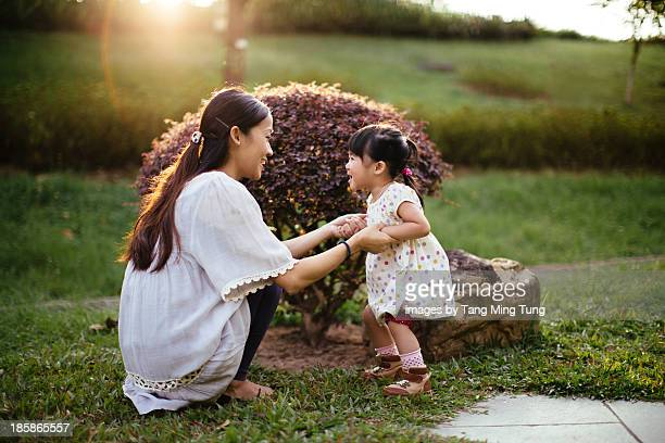 Mom playing joyfully with toddler girl on lawn