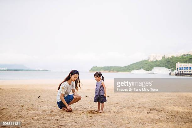 Mom playing sand with child on beach