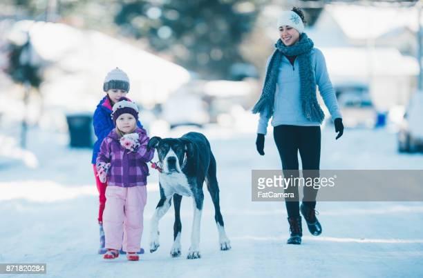 Mom Playing With Young Girls on Snowy Neighborhood Street