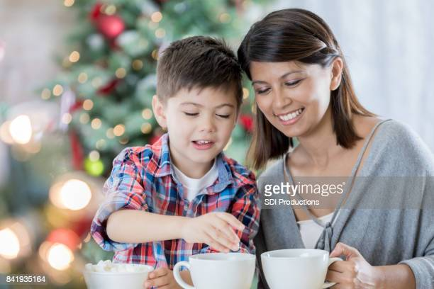 mom prepares cocoa with young son - filipino christmas family stock pictures, royalty-free photos & images