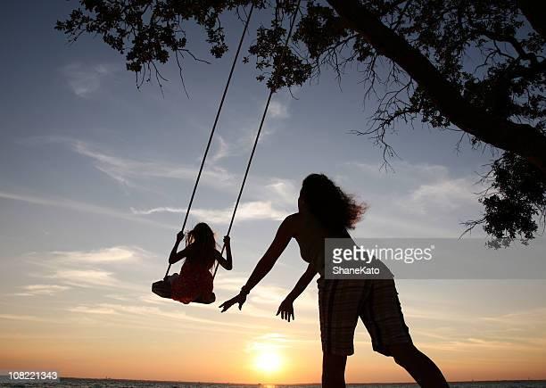 Hört Mutter und Tochter Spielen auf der Schaukel mit Sonnenuntergang silhouette