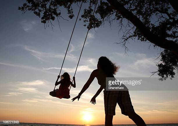 Madre hija insiste en juego colgante de silhouette playing at sunset