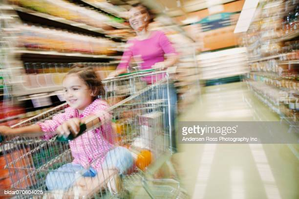 Mom pushing daughter in cart in grocery aisle (blur)