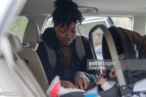 MOM bringt ihr Säugling Baby in den Autositz