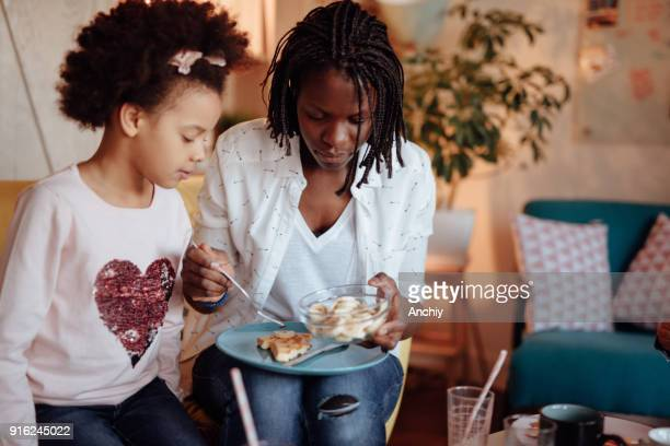 mom putting bananas on her daughter waffle - interracial cartoon stock photos and pictures