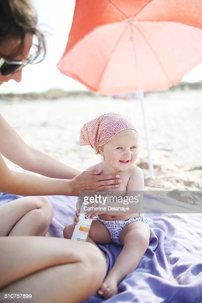 A mom putting sunscreen on her baby girl