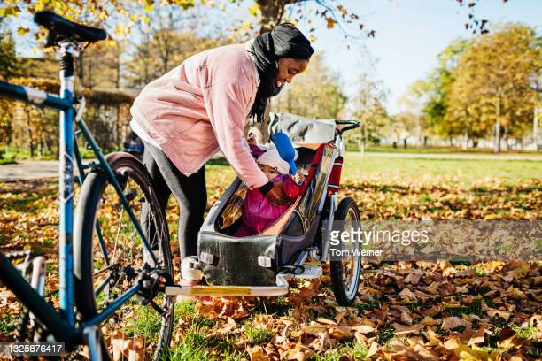 mom putting toddler into trailer attached to bicycle - bicycle stock pictures, royalty-free photos & images