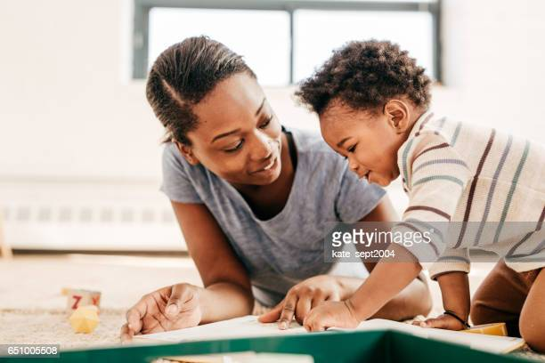 mom reading for toddler - black mothers day stock pictures, royalty-free photos & images