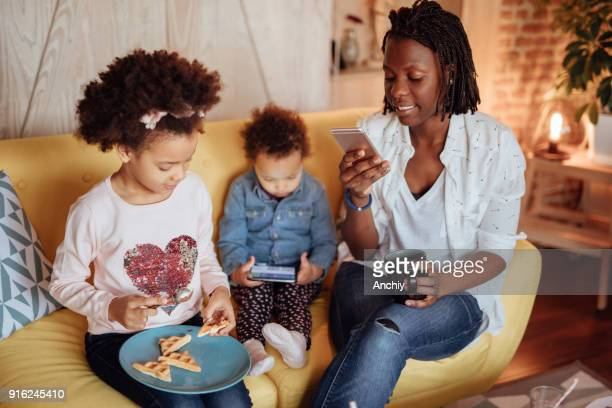 mom reading text messages while her kids sits next to her - interracial cartoon stock photos and pictures