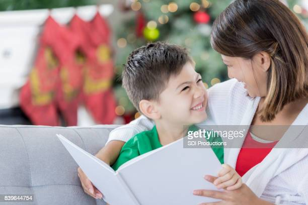 mom reads her young son a story at christmastime - filipino christmas family stock pictures, royalty-free photos & images