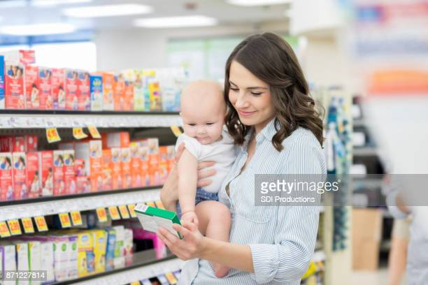 mom reads label on over the counter medication - consumerism stock pictures, royalty-free photos & images