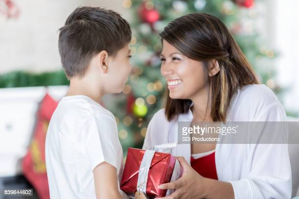 mom receives christmas gift from son - filipino christmas family stock pictures, royalty-free photos & images