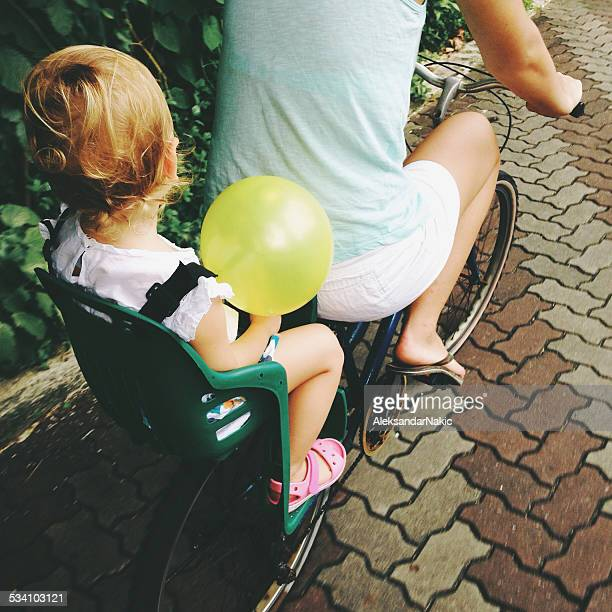 Mom rides daughter on a bicycle at their vacation