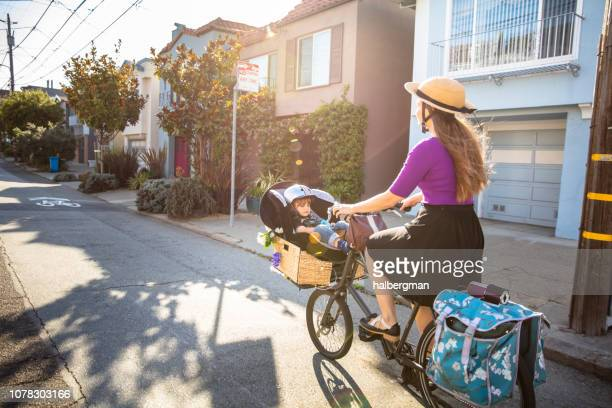 Mom Riding Bike Along Residential Street with Baby in Basket