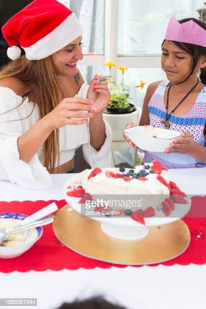 Mom serves pavlova to daughter at Christmas table