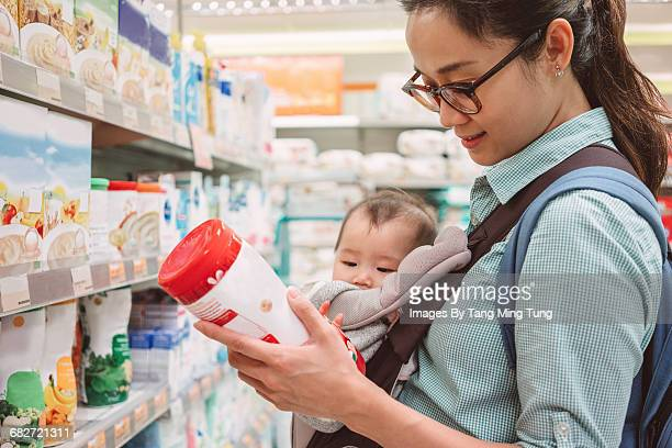 Mom shopping baby food with baby joyfully