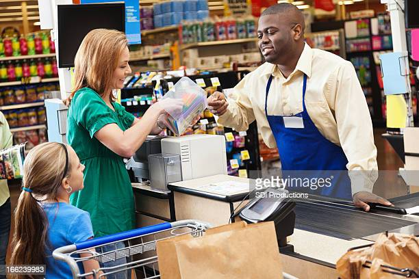 Mom shopping for groceries with daughter, checking price on item