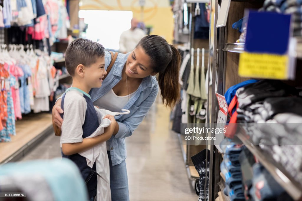 Mom shops for school clothes with her son : Stock Photo