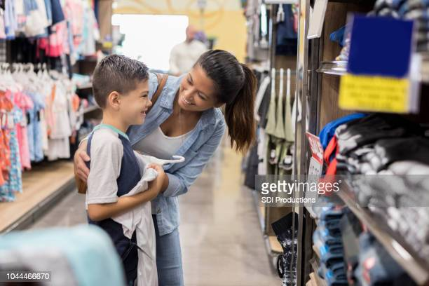 mom shops for school clothes with her son - riapertura delle scuole foto e immagini stock