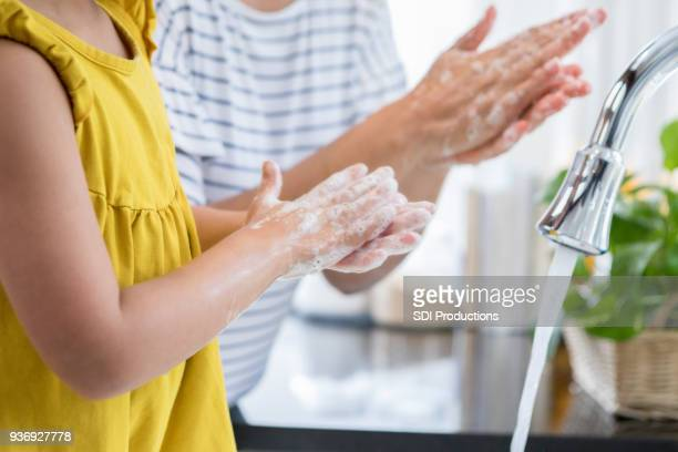 mom shows daughter proper way to wash hands - washing hands stock pictures, royalty-free photos & images
