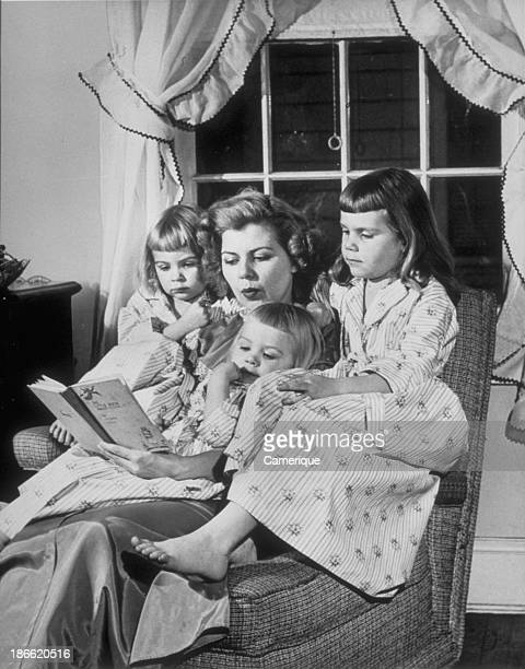 Mom siitting on chair with her 3 girls reading to them 1964