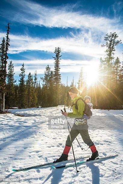 mom skiing with toddler - langlaufen stockfoto's en -beelden