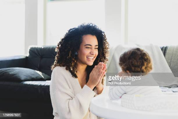 mom smiles while teaching baby to clap - clapping hands stock pictures, royalty-free photos & images