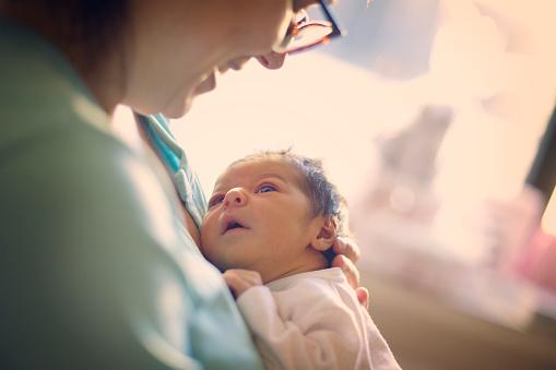 Mom smiling at newborn at hospital - gettyimageskorea
