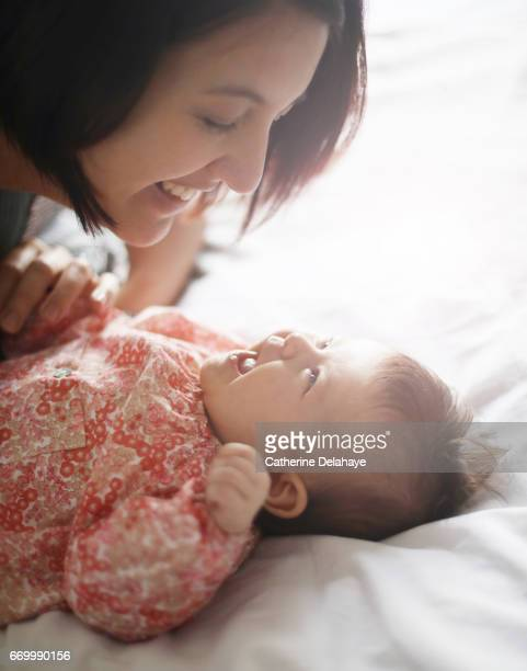 A mom smiling to her 2 months old baby girl
