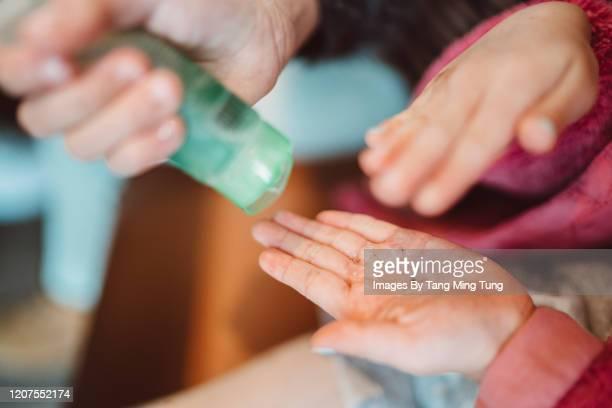 mom squeezing hand sanitizer onto her littler daughter's hands - hand sanitizer fotografías e imágenes de stock
