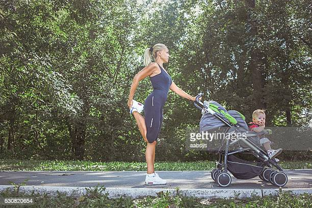 Mom stretching while holding stroller.