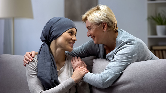Mom supporting and hugging her daughter with cancer, visits in oncohospital 1143447712