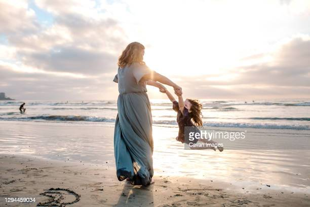 mom swinging young daughter by the arms on the beach at sunset - maxi jurk stockfoto's en -beelden
