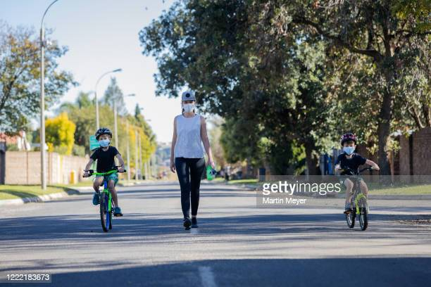 mom taking her 2 boys out in the streets for exercise in south african suburb - pedestrian stock pictures, royalty-free photos & images