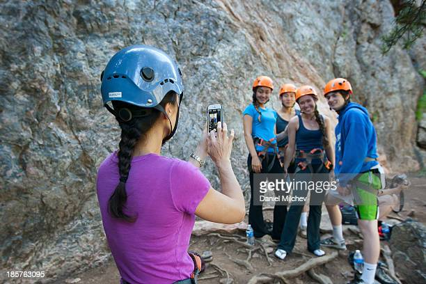 Mom taking photo of her kids and friends climbing.