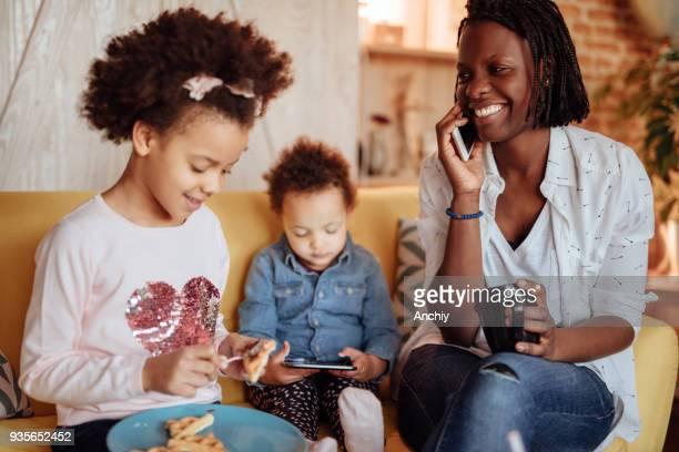 ママの娘が朝食を食べている間電話で話しています。