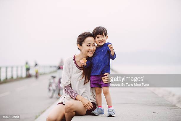 Mom talking to little girl joyfully on embankment