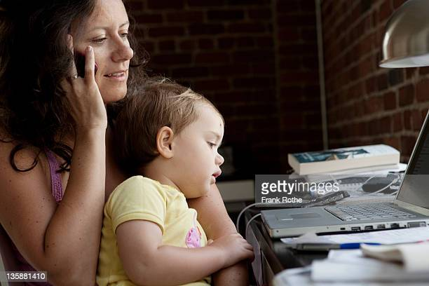 mom talks on the phone while working on the laptop