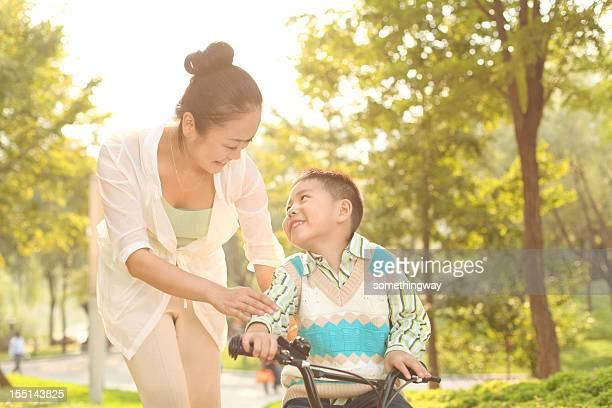 Mom taught his son in the park riding a bike