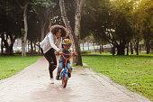 Mom teaching her son biking at park