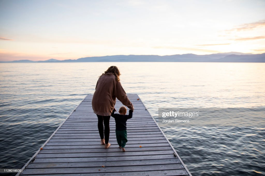 A mom teaching her young son to walk on a dock. : Stockfoto