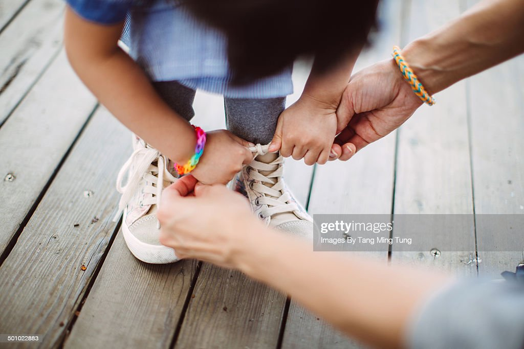 Mom teaching little girl to tide her shoelace : Stock Photo