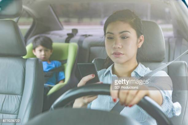 mom texts while driving with child in the backseat - driving stock pictures, royalty-free photos & images