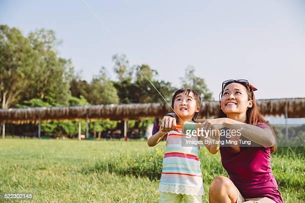 Mom & toddler flying kite in country park