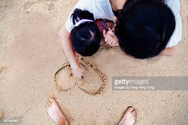 Mom & toddler girl drawing in the sand