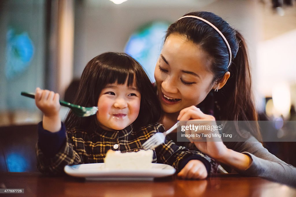 Mom & toddler girl having cake joyfully in cafe : Stock Photo